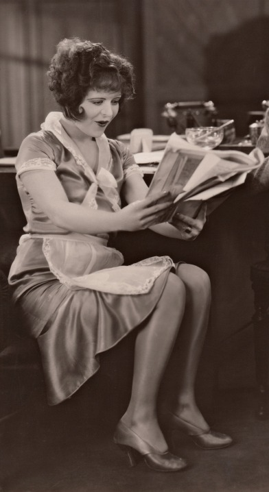 Clara reading the paper, 1928. As Bubbles McCoy in Red Hair.